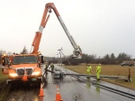 Crews work to fix power poles in Middlebury blown down by strong winds on Friday.