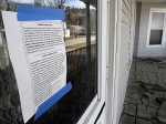 A notice of vacancy is seen on a flood-damaged house on Water Street in Northfield.
